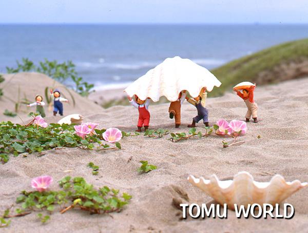 はまひるがお の咲く海辺の白浜で貝殻を運ぶ小人たち